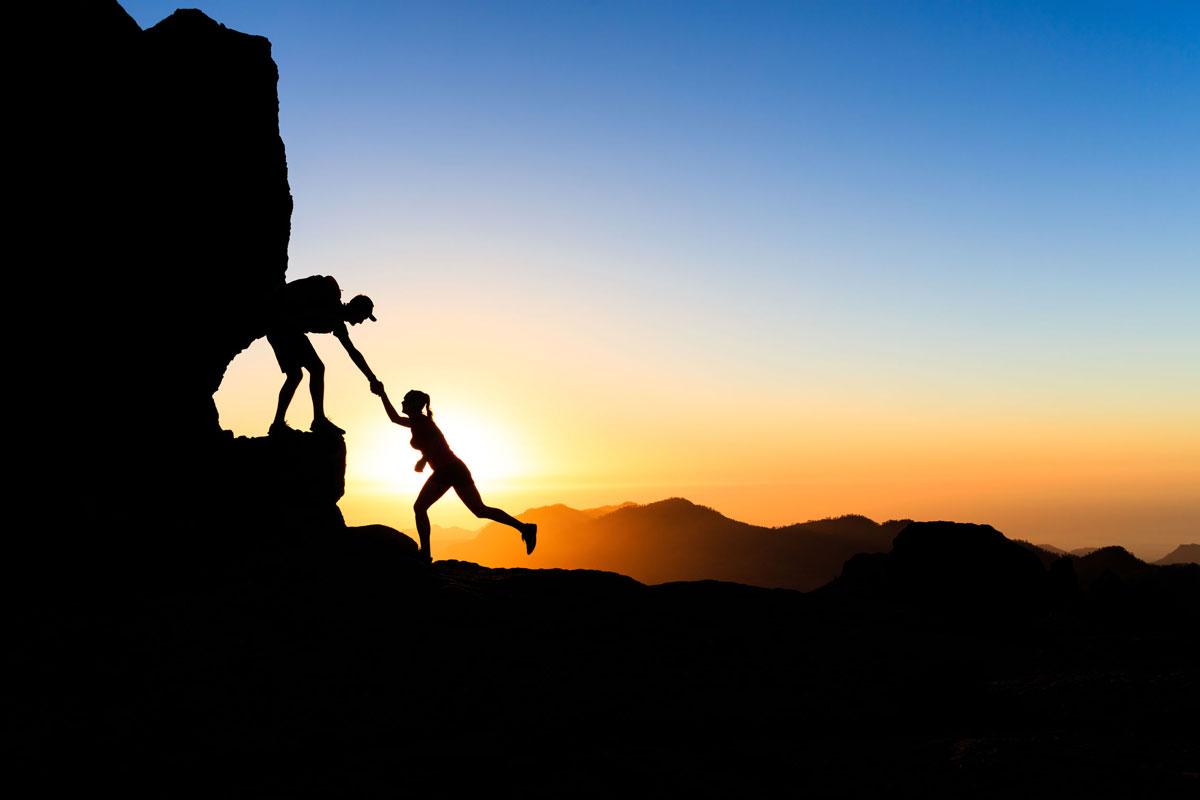 Bergsteiger im Sonnenuntergang helfen einander